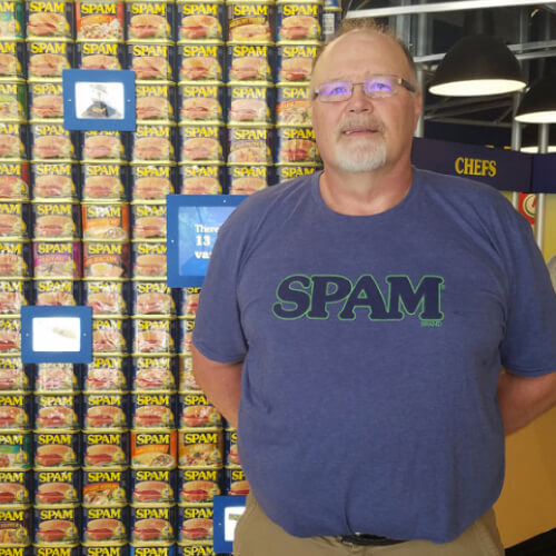 SPAMbassador Jeff in SPAM museum in front of SPAM cans.
