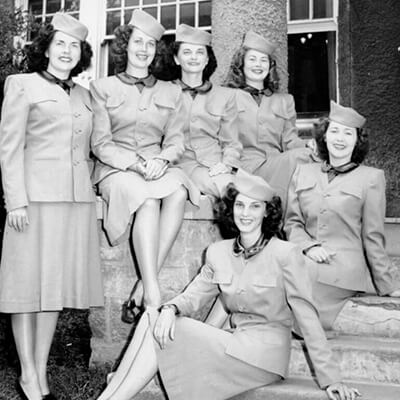 6 women in uniforms sit on a staircase in 1947.