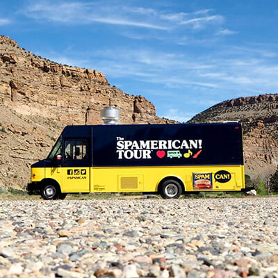 The SPAMERICAN Tour truck in front of mountains.